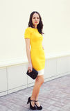 Beautiful young woman in yellow dress with black handbag Royalty Free Stock Image