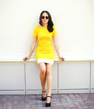 Beautiful young woman in yellow dress and black sunglasses Stock Images