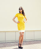 Beautiful young woman in yellow dress and black sunglasses Royalty Free Stock Photo