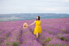 Beautiful young woman in yellow dress running happy in violet flower lavander field royalty free stock photo