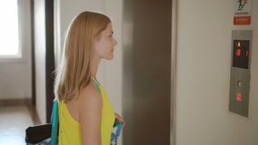 Beautiful young woman in yellow dress waiting for an elevator. Pushing a button calling up a lift.  stock footage