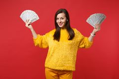 Beautiful young woman in yellow fur sweater holding fan of money in dollar banknotes, cash money isolated on bright red. Wall background. People sincere stock images