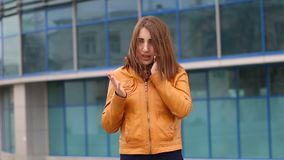 Beautiful young woman in yellow jacket is standing and talking on cell phone outdoor in the city stock video footage