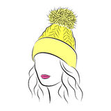 Beautiful young woman in yellow knitted hat with pompom. Close up portrait. Beautiful young woman in yellow knitted hat with pompom. Bright lips painted on her Royalty Free Stock Photography