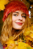 Beautiful young woman among yellow leaves Stock Images