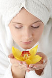 Beautiful young woman with yellow orchid Stock Photos