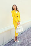 Beautiful young woman in yellow suit clothes with handbag Royalty Free Stock Photo