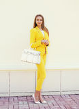 Beautiful young woman in yellow suit clothes with handbag posing Stock Photography