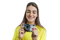 Beautiful young woman in yellow sweater holding vintage camera in her hands, smiling, taking pictures, looking with interest. Whit royalty free stock photo