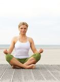 Beautiful young woman in yoga pose at beach royalty free stock photo