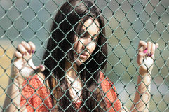 Beautiful young women. Beautiful young woman against fence Stock Photography