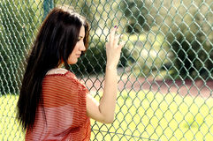 Beautiful young women against fence. Beautiful young woman against fence. unhappy beautiful girl Stock Images