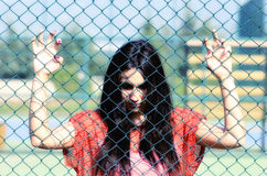 Beautiful young women against fence. Beautiful young woman against fence. unhappy beautiful girl Royalty Free Stock Photography