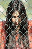Beautiful young women against fence Royalty Free Stock Photography