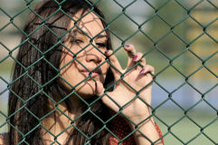 Beautiful young women against fence Royalty Free Stock Image