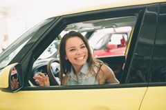 Beautiful young woman buying a car at dealership. Female model sitting Sits in the car interior. Beautiful young women buying a car at dealership. Female model Stock Images