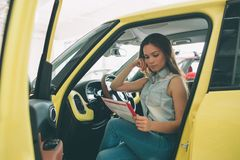Beautiful young woman buying a car at dealership. Female model sitting Sits in the car interior. Beautiful young women buying a car at dealership. Female model Stock Photo