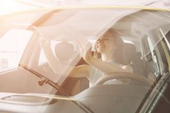 Beautiful young woman buying a car at dealership. Female model sitting Sits in the car interior. Beautiful young women buying a car at dealership. Female model Royalty Free Stock Photo
