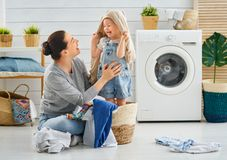 Family doing laundry. Beautiful young women and child girl little helper are having fun and smiling while doing laundry at home royalty free stock photography