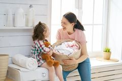 Family doing laundry. Beautiful young women and child girl little helper are having fun and smiling while doing laundry at home stock images