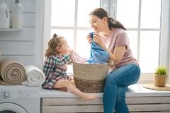 Family doing laundry. Beautiful young women and child girl little helper are having fun and smiling while doing laundry at home stock image