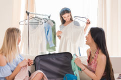 Beautiful young women choosing clothes and packing suitcase for travel Stock Image