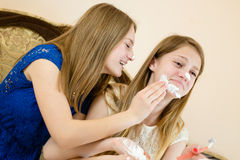 2 beautiful young women cute blond sisters or girls friends having fun together in blue and white dress smearing shaving foam. Two blond sisters or girls friends Royalty Free Stock Image