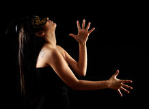 Beautiful young women dancing. Young mystery woman standing in black venetian mask. attractive beautiful young women dancing. isolated black background Stock Photo