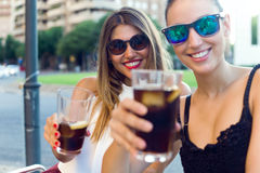 Beautiful young women drinking refreshment in the street. Stock Photography