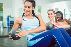 Beautiful woman exercising Russian twist with med ball for strong abs. Beautiful young women exercising Russian twist with med ball from sitting position for stock photography