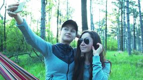 Beautiful young women in the forest do selfie on a hammock. Tourists on vacation using a smartphone do selfie, smiling. stock video footage