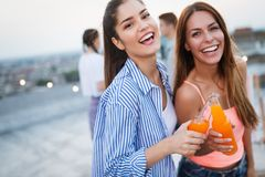 Beautiful women friends on the balcony having fun at party. royalty free stock images