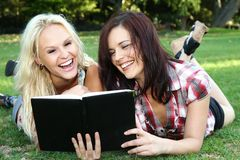 Beautiful Young Women Friends Reading Outdoors Stock Images