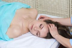 Beautiful young woman getting facial massage in the beauty salon