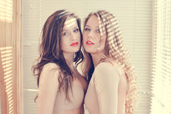2 beautiful young women girl friends in bodily costumes with red lips standing against sun lighting Royalty Free Stock Image