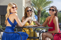 Beautiful Young Women Having Coffee At City Cafe. Three beautiful and sophisticated young women friends wearing sunglasses and having coffee around a modern city Royalty Free Stock Photos