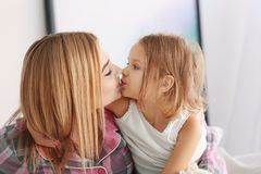 Beautiful young woman and her daughter at home. Beautiful young women and her daughter at home. Mother`s day concept Stock Photo