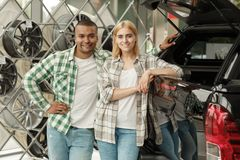 Happy couple buying new car together at the dealership. Beautiful young women and her handsome boyfriend embracing near their new automobile at the dealership stock image