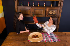 Beautiful young women holding a bottle of tequila and standing a. T bar counter in Mexican pub, a shelf with spicy sauces in the background stock photos