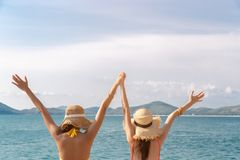 Beautiful young women holding hands, raise up hands together. They are friend and always love traveling together when they get stock photo