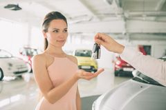 Beautiful young woman is holding a key in car dealership. Auto business, car sale, - happy female model in auto show or. Beautiful young women is holding a key Royalty Free Stock Photos