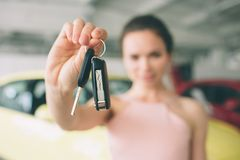 Beautiful young woman is holding a key in car dealership. Auto business, car sale, - happy female model in auto show or. Beautiful young women is holding a key Royalty Free Stock Photo