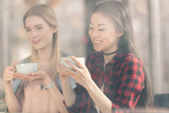 Beautiful young women holding white cups and drinking fresh coffee. Coffee break concept royalty free stock photos