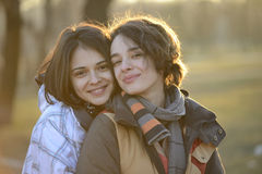 Beautiful young women hugging outside Stock Photos