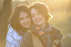 Beautiful young women hugging outside Stock Images