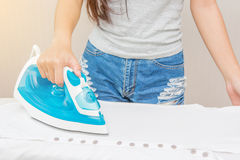 Beautiful young women ironing a shirt Royalty Free Stock Image