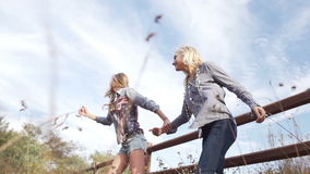 Beautiful young women jumping across fence running. Two beautiful young women jumping across fence and running away