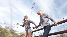 Beautiful young women jumping across fence running stock video