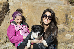 Beautiful young women laughing and  hugging dog. Happy friends   hugging dog outdoor Royalty Free Stock Images