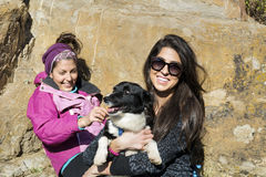 Beautiful young women laughing and  hugging dog. Happy friends   hugging dog outdoor Stock Images